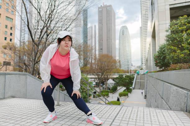 市内でストレッチを行う女性 - real bodies ストックフォトと画像