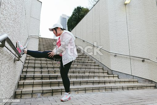 851958232 istock photo Woman doing stretching in city 938508598