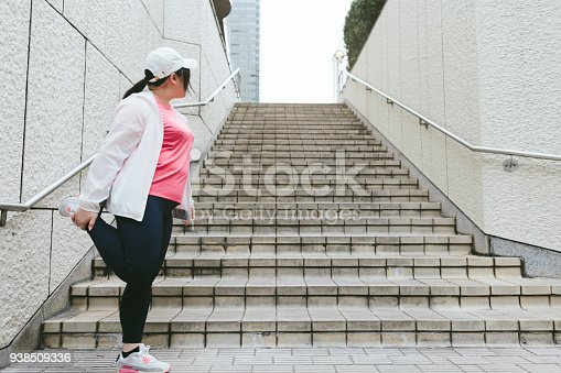 851958232 istock photo Woman doing stretching in city 938509336