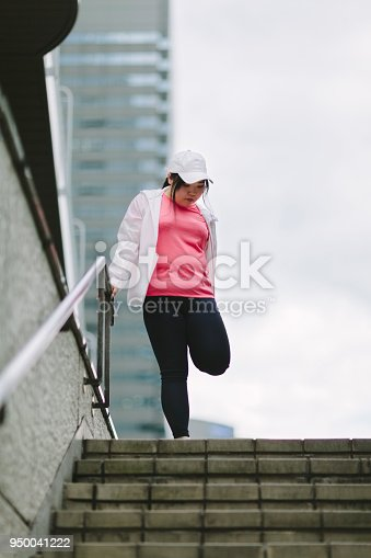 851958232 istock photo Woman doing stretching in city 950041222