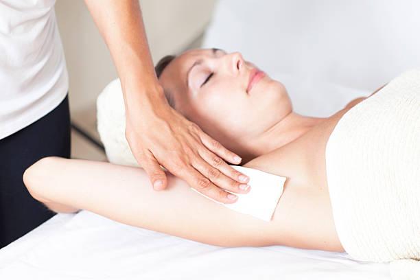 Woman doing the armpit depilation stock photo