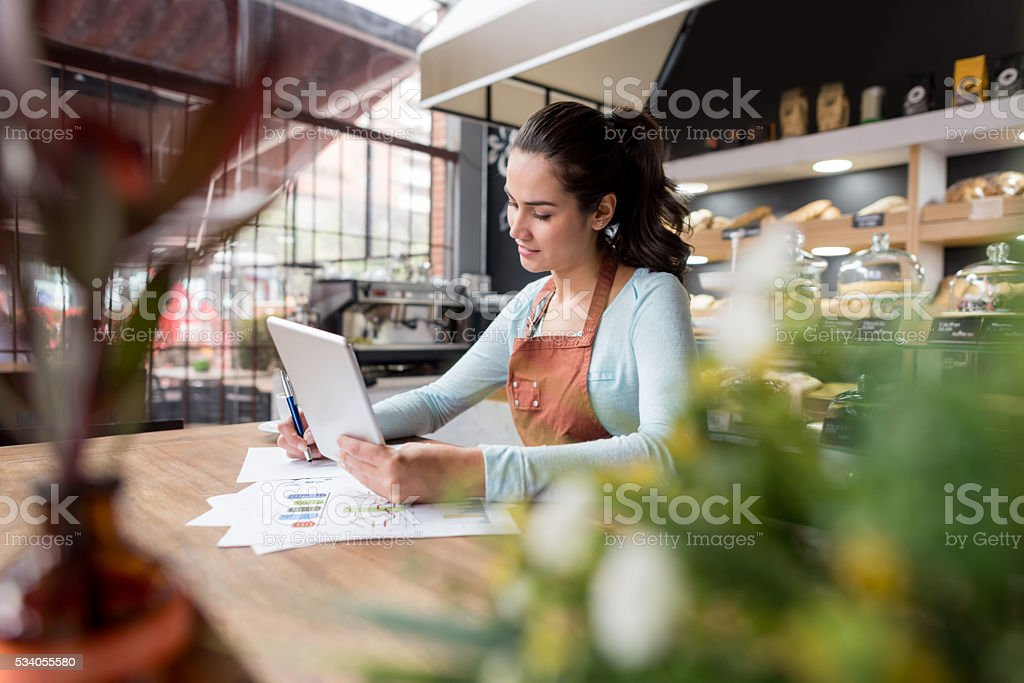 Woman doing the books at a restaurant stock photo