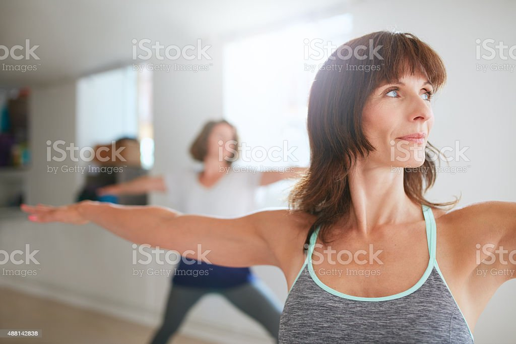 Woman doing the warrior pose during yoga class stock photo