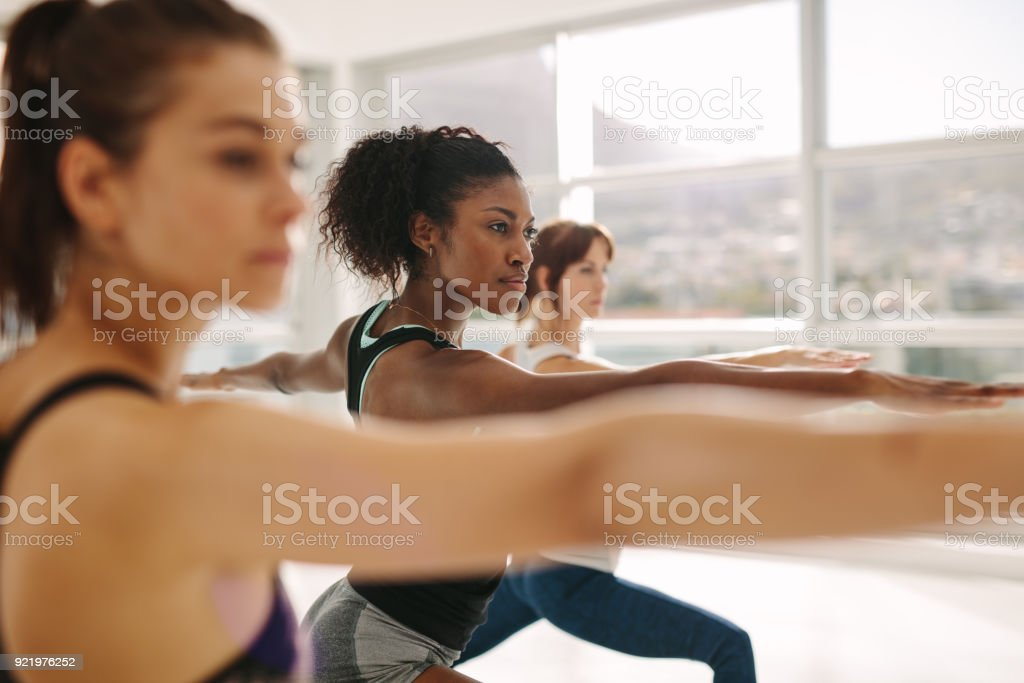 Woman doing the warrior pose during yoga class. stock photo