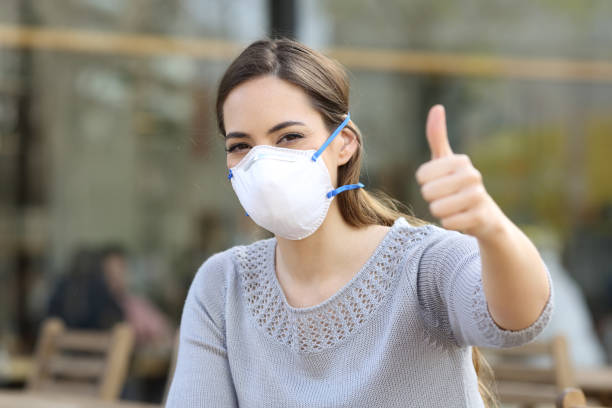 Woman doing thumbs up wearing protective mask stock photo