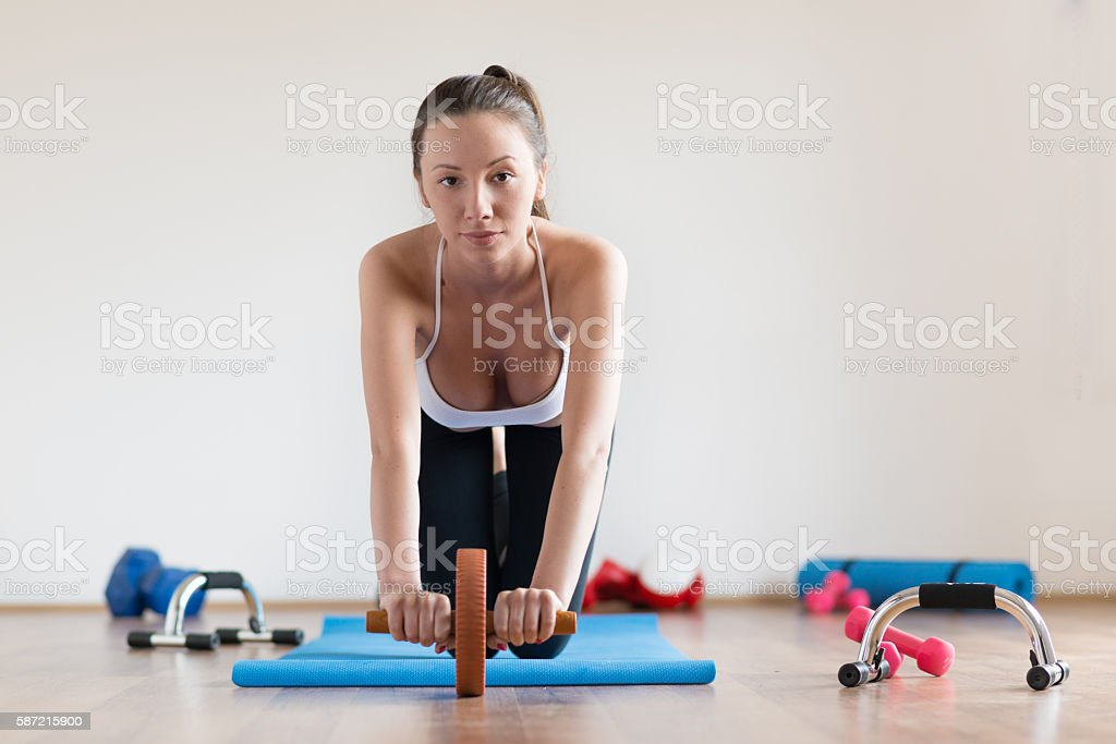 Woman doing training with abs roller wheel. stock photo