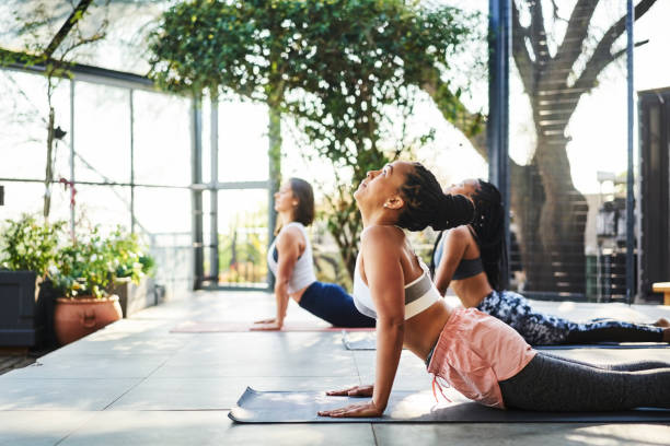 Woman doing Upward Facing Dog Pose with friends Side view of mid adult woman doing Upward Facing Dog Pose with friends. Multi-ethnic fit females are exercising at yoga studio. They are representing healthy lifestyle. upward facing dog position stock pictures, royalty-free photos & images