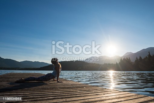 Full length of woman doing upward facing dog position on pier by Lake Alta. Side view of female athlete is practicing yoga against blue sky. She is wearing sports clothing