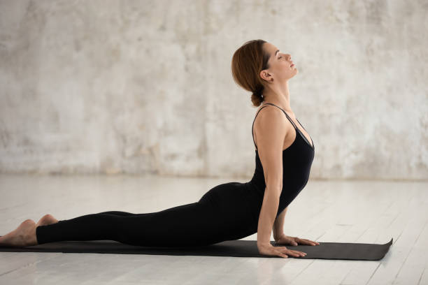 Woman doing Urdhva Mukha Svanasana or Upward Facing Dog pose Woman in black sportswear performs yoga doing Urdhva Mukha Svanasana or Upward Facing Dog pose working out indoors studio shot, side view, healthy lifestyle physical mental spiritual practice concept upward facing dog position stock pictures, royalty-free photos & images