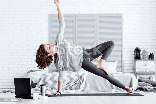istock Woman doing vasisthasana yoga pose at home 1152160922