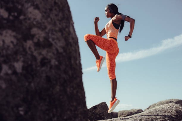 woman doing warm up exercises outdoors - lunge stock photos and pictures