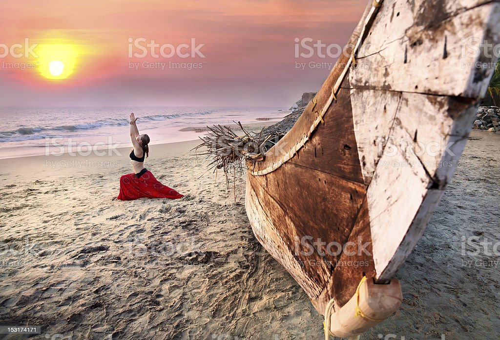 Woman doing warrior yoga pose by a boat on a beach at sunset stock photo