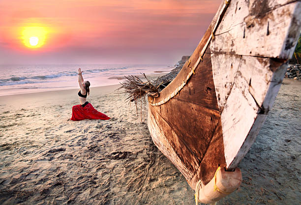 Woman doing warrior yoga pose by a boat on a beach at sunset Beautiful woman doing virabhadrasana warrior yoga pose on the beach near the ocean on sunset in India goa stock pictures, royalty-free photos & images