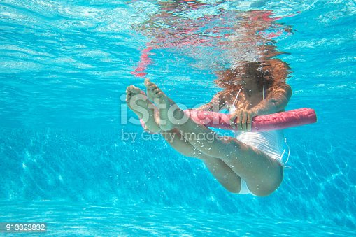 sporty woman doing water aerobics in a pool with a buoy