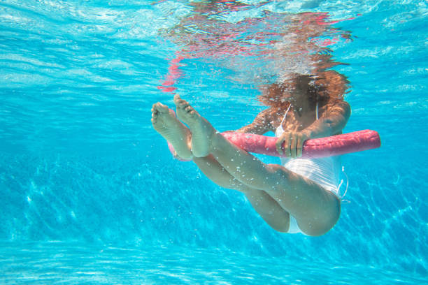 woman doing water aerobics in a pool - acquagym foto e immagini stock