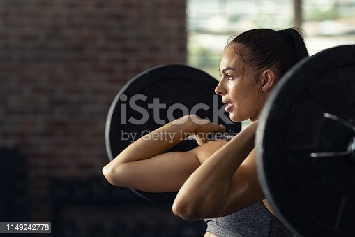 Fitness woman doing shoulder press exercise with a weight bar at cross training gym. Muscular woman in gym doing heavy weight exercises. Concentrated athlete doing barbell lifting at health club with copy space.