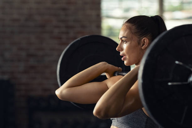 woman doing weight lifting at gym gym - pesistica foto e immagini stock