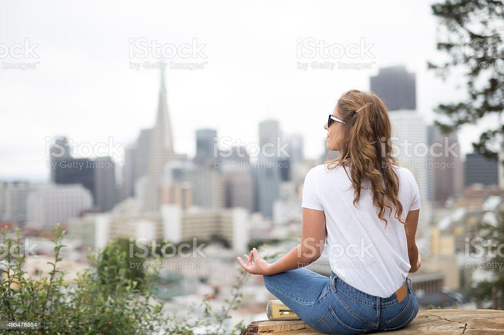 Woman Doing Yoga and facing the San Francisco Downtown stock photo