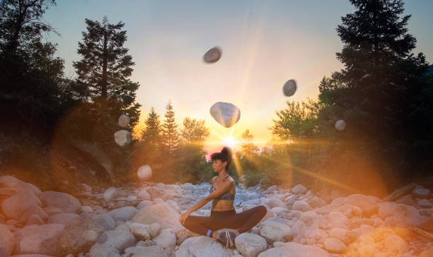 Woman doing yoga and floating rocks stock photo