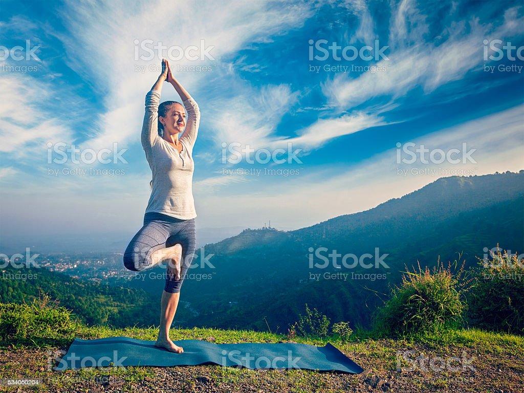 Woman doing yoga asana Vrikshasana tree pose in mountains outdoors stock photo