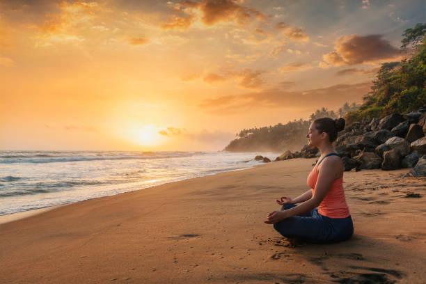 Woman doing yoga at beach - Padmasana lotus pose Woman doing yoga - meditate and relax in Padmasana Lotus asana pose with chin mudra outdoors at tropical beach on sunset with dramatic sun yogi stock pictures, royalty-free photos & images