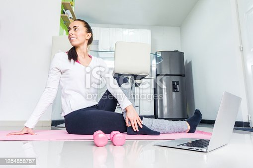 Young Latin American Woman doing yoga at home following an online tutorial during the COVID-19 pandemic