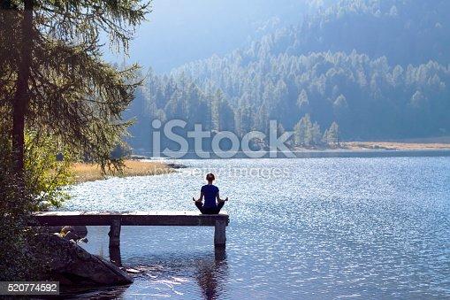 istock Woman doing yoga at lake 520774592