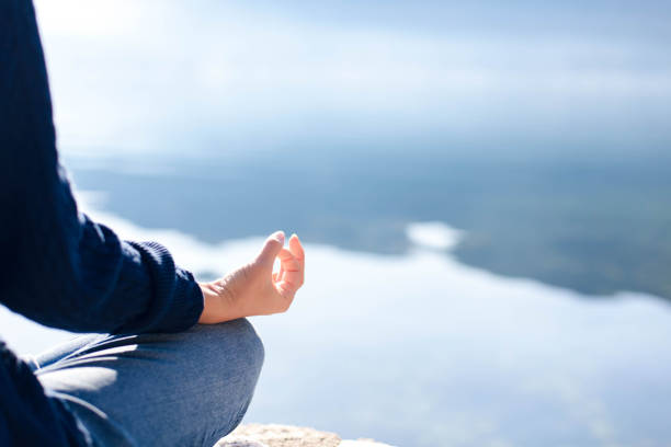 Woman doing yoga at sea beach. Blue background, copy space. Girl practicing meditating stock photo
