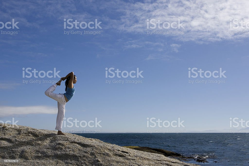 Woman doing yoga at the ocean royalty-free stock photo