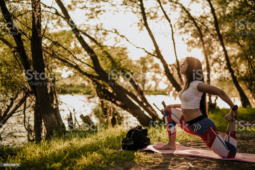 Woman doing yoga exercise by the river royalty-free stock photo