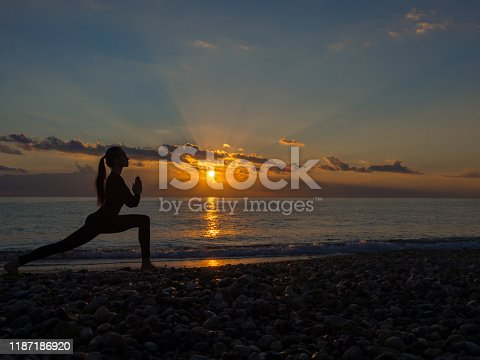 873786782istockphoto Woman doing yoga exercise during sunset on the beach. 1187186920