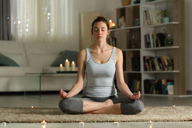 Woman doing yoga exercise in the night at home with candles stock photo