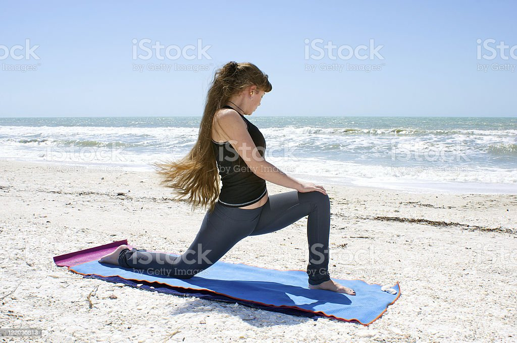woman doing yoga exercise on beach rotated Low Lunge stock photo