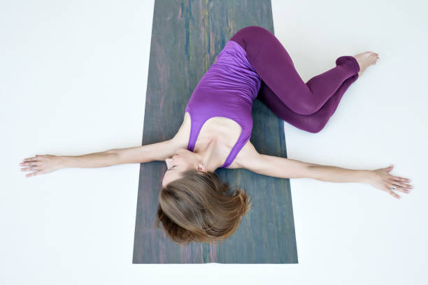 woman doing yoga exercise on floor variation of belly twist pose - twisted stock pictures, royalty-free photos & images