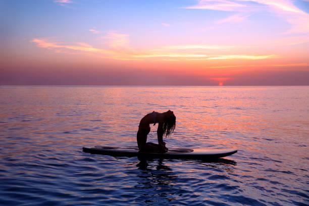 frau tun yoga übung - stehpaddeln stock-fotos und bilder