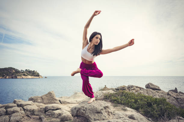 Woman doing yoga exercises at the sea Young woman doing yoga at the sea yogi stock pictures, royalty-free photos & images