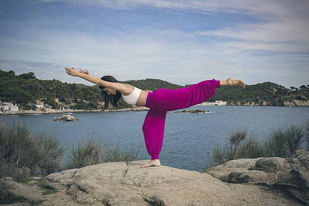 Woman doing yoga exercises at the sea Warrior 3 pose stock photo