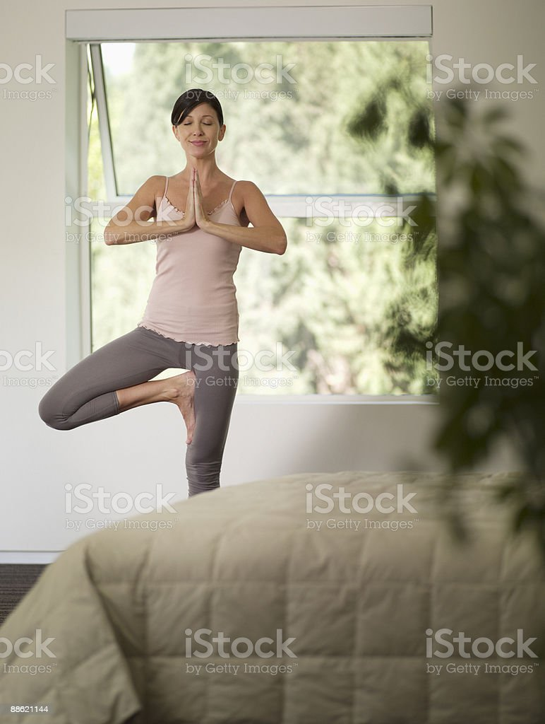 Woman doing yoga in bedroom royalty-free stock photo