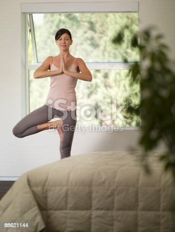 Woman Doing Yoga In Bedroom Stock Photo & More Pictures of 40-44 Years