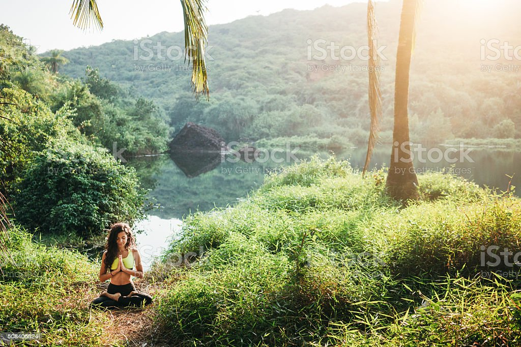 Woman doing yoga in jungles stock photo