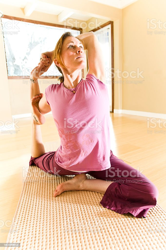 Woman doing yoga in studio with morning light stock photo