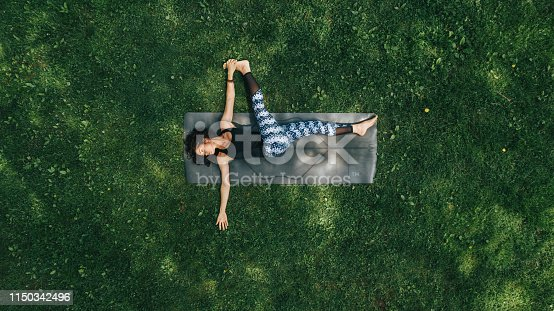 istock Woman doing Yoga in the Park 1150342496