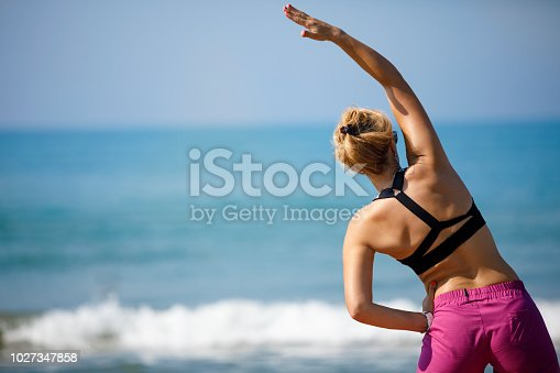 816941230istockphoto Woman doing yoga meditation and stretching exercises on the beach 1027347858