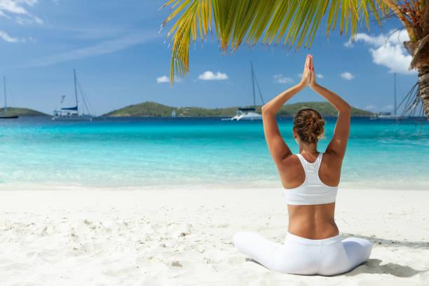 woman doing yoga meditation on a tropical beach