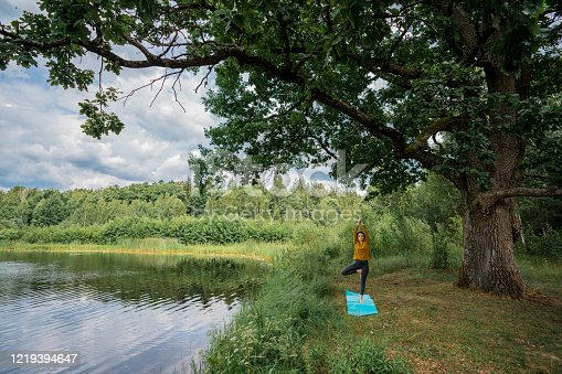 Young Caucasian woman doing yoga near the old oak by the lake