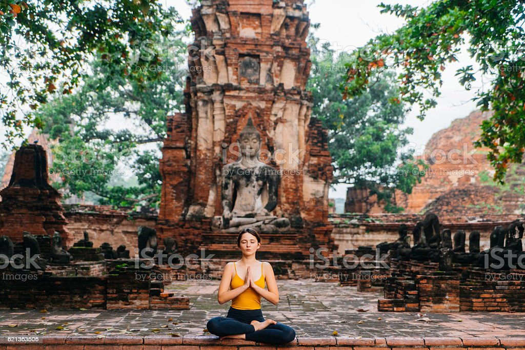 Woman doing yoga near the ruins of Buddhist Temple stock photo