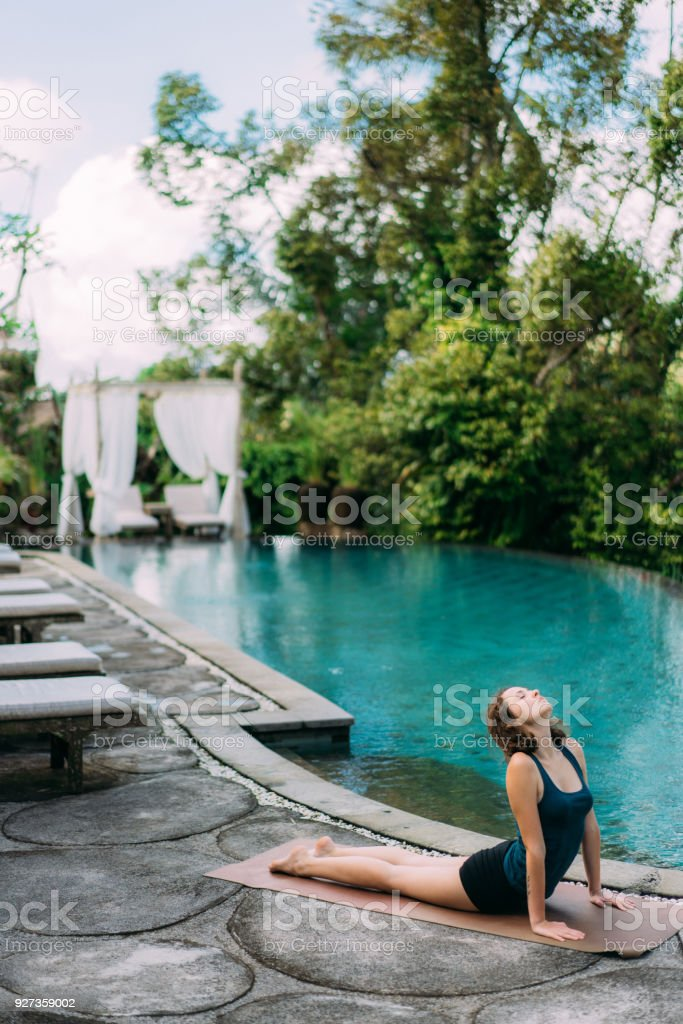 Woman doing yoga near the swimming pool - Royalty-free 20-24 Years Stock Photo