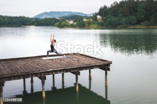 Woman doing yoga on the wooden jetty by the lake. Warrior One pose (Virabhadrasana I).