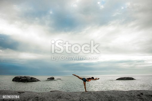 Shoot for a woman on a rock on a beach at sunset
