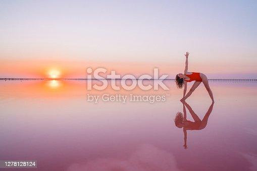 istock Woman doing yoga  on pink salt lake in Ukraine 1278128124